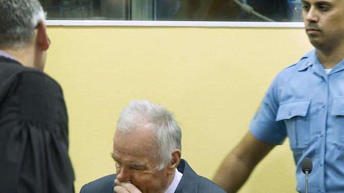 Former Bosnian Serb military commander Gen. Ratko Mladic, center, a UN security guard, right, and member of his defense, left, are seen at the start of his trial at the Yugoslav war crimes tribunal in The Hague, Netherlands, Wednesday May 16, 2012. Twenty years after the opening shots of the Bosnian War, Mladic has gone on trial on charges of genocide, crimes against humanity and war crimes, his appearance at the UN tribunal marks the end of a long wait for justice to survivors of the 1992-95 war that left some 100,000 people dead. (AP Photo/Toussaint Kluiters, Pool)