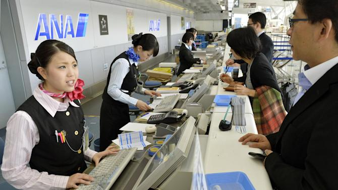 Employees deal with passengers at the counter at Sendai Airport in Sendai, northern Japan after flights in and out of the airport were canceled Tuesday, Oct. 30, 2012. The airport has been closed after an unexploded bomb believed to be from World War II was found during construction near a runway. (AP Photo/Kyodo News) JAPAN OUT, MANDATORY CREDIT, NO LICENSING IN CHINA, FRANCE, HONG KONG, JAPAN AND SOUTH KOREA