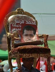 An Egyptian man holds a chair with a portrait of president-elect Mohamed Morsi during a rally in Cairo's Tahrir Square