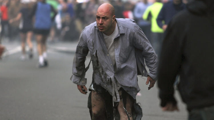 In this photo provided by The Daily Free Press and photographer Kenshin Okubo, Boston Marathon bombing victim James Costello staggers away in his torn clothing from the finish area in Boston, Monday, April 15, 2013. (AP Photo/The Daily Free Press, Kenshin Okubo) MANDATORY CREDIT