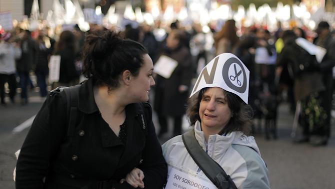 """A woman marches as she displays a banner reading, """"I am deaf and blind, the interpreters are my ears, my eyes and my voice, with them everything is possible """" and """"No financial cuts"""" during a protest against government austerity measures affecting disabled people by reducing services, closing disability centers and forcing care workers from their jobs in Madrid, Spain, Sunday, Dec. 2, 2012. More than 10,000 people, many in wheelchairs or being led by guide dogs, marched in a demonstration with the slogan """"SOS Disability: Save our Rights, Inclusion and Welfare."""" Health care spending falls under the responsibility of regional governments, many of which are indebted. Some local administrations have failed to pay medical centers, forcing cuts in services and a slow-down in the distribution of medicine. (AP Photo/Andres Kudacki)"""