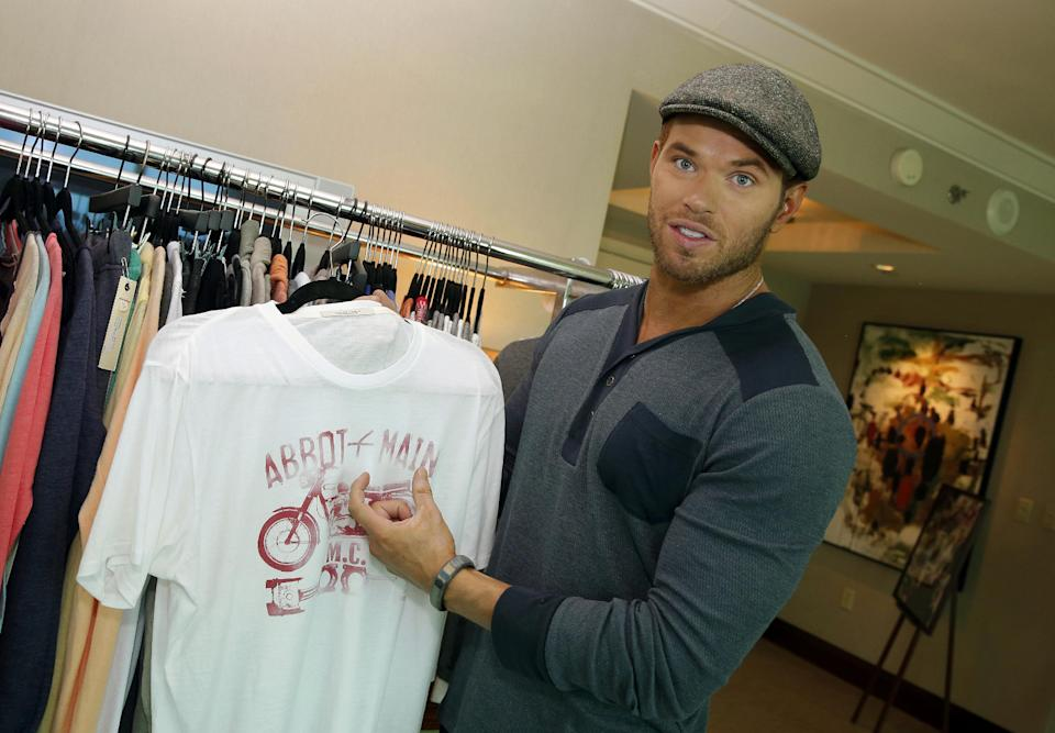 Actor and designer Kellan Lutz holds up an item from his pre-spring 2014 clothing line Abbot + Main at the Mandalay Bay Hotel on Monday, Aug. 19, 2013 in Las Vegas. (Photo by Isaac Brekken/Invision/AP)