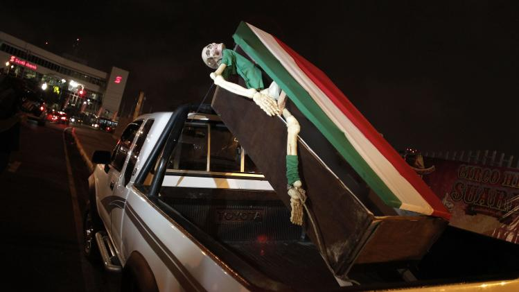 A Costa Rica fan displays a coffin on the back of his pickup truck outside the National Stadium before a practice session for Mexico's national soccer team in San Jose