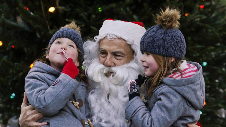 Children present their wishes to a man dressed as Santa Claus at a local park during Christmas activities in New York