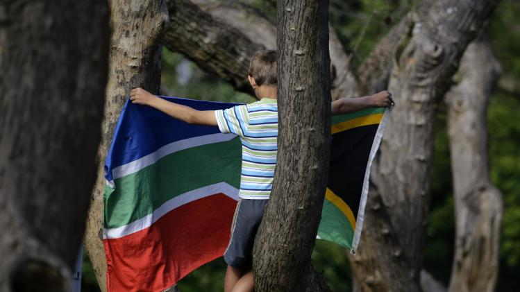 A boy holds South Africa's national flag as he waits up a tree for the funeral cortege carrying the coffin of former South African President Nelson Mandela to arrive at the Union Buildings in Pretoria