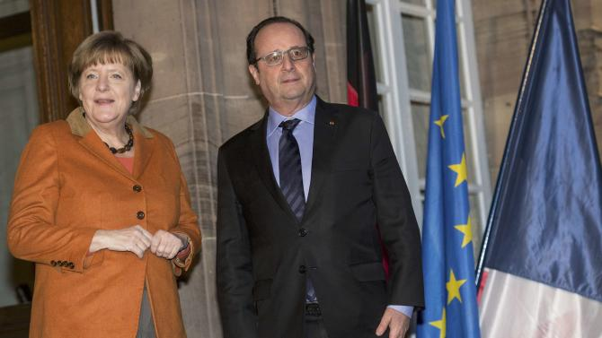 French President Francois Hollande and German Chancellor Angela Merkel stand outside the Prefecture in Strasbourg