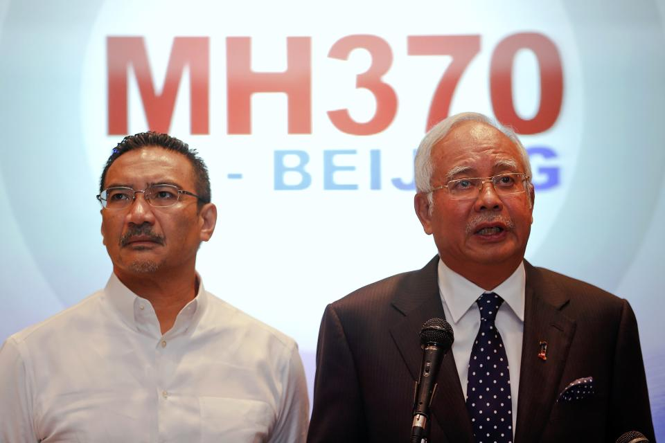 Malaysian PM Najib addresses reporters as Transport Minister Hussein stands by him, at Kuala Lumpur International Airport