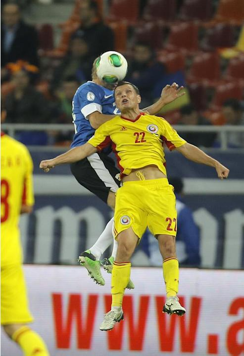 Taijo Teniste, top left, of Estonia and Gheorghe Bucur of Romania, front right, jump for a header during the World Cup Group D qualifying soccer match at the National Arena stadium in Bucharest, Roman