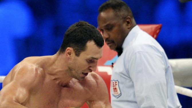 Heavyweight champion  Wladimir Klitschko of Ukraine, left, knocked down  contender Tony Thompson, of the United States, right, during their world heavyweight championship title bout at the Stade de Suisse soccer stadium in Bern, Switzerland, Saturday, July 7, 2012.  Wladimir Klitschko stopped Tony Thompson in the sixth round to retain his WBA, IBF and WBO heavyweight title belts on Saturday. (AP Photo/Keystone/Alessandro della Valle)