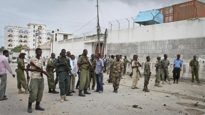 Somali government soldiers gather in front of the main U.N. compound, following an attack on it in Mogadishu, Somalia Wednesday, June 19, 2013. Al-Qaida-linked militants detonated multiple bomb blasts and engaged in ongoing battles with security forces in an attempt to breach the main U.N. compound in Mogadishu, officials said Wednesday. (AP Photo/Farah Abdi Warsameh)