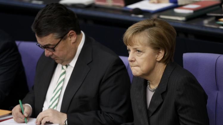 German Chancellor Merkel sits next to Economy Minister Gabriel before addressing in Berlin