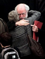 "Archbishop of Canterbury Rowan Williams hugs a female member of the clergy at Church House in central London on November 20. The Church of England has ""undoubtedly"" lost credibility after voting to reject the appointment of women bishops, its leader the Archbishop of Canterbury said Wednesday."