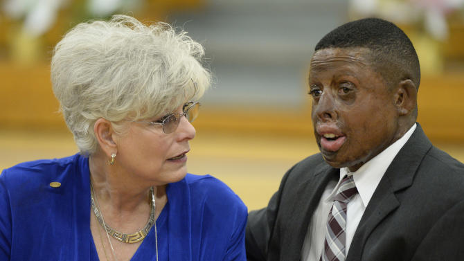 Karolyn Nunnallee, left, mother of Carrolton bus crash victim Patricia Nunnallee, speaks with Harold Dennis during the memorial service on the 25th anniversary of the Carrolton bus crash at North Hardin High School May 14, 2013 in Radcliff, Ky. (AP Photo/Timothy D. Easley)