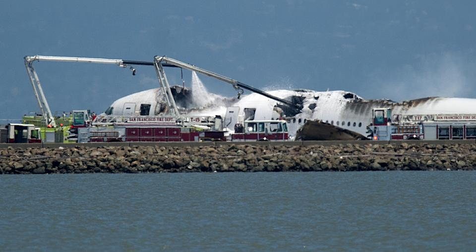 A fire truck sprays water on Asiana Flight 214 after it crashed at San Francisco International Airport on Saturday, July 6, 2013, in San Francisco. (AP Photo/Noah Berger)