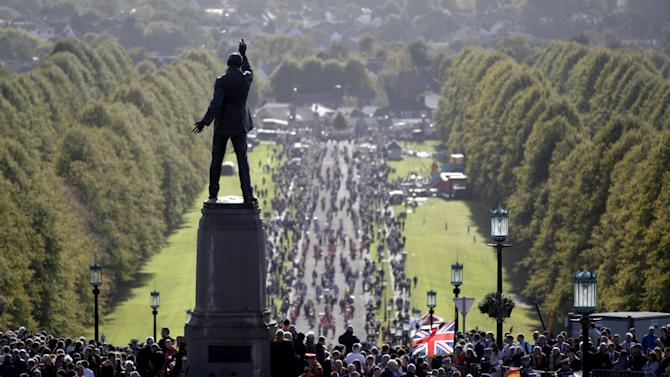 Thousands of Orange men and women parade past the statue of Edward Carson at Parliament Buildings, Stormont, Northern Ireland, Saturday, Sept. 29, 2012. Thousands Protestant people are taking part in commemorations in Belfast to mark one of the most significant dates in unionist history. The six-mile march from central Belfast to Stormont marks the 100th anniversary of the Ulster Covenant, to oppose Home Rule for Ireland in 1912.  (AP Photo/Peter Morrison)