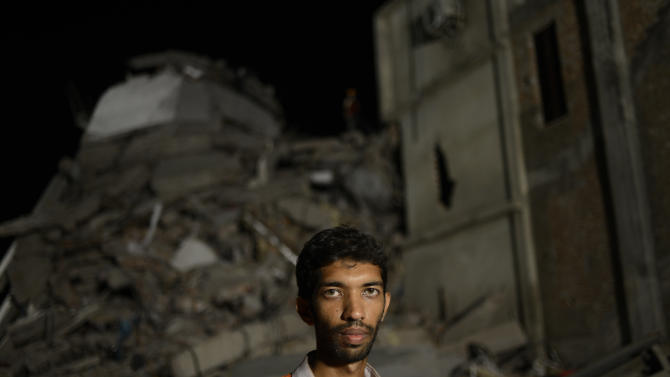 Saiful Islam Nasar poses in front of the rubble of a building collapse in Savar, near Dhaka, Bangladesh Monday April 29, 2013. Nasar, a mechanical engineer is one of hordes of volunteers who came to Savar to help with the rescue effort. They get no funding, have no training and buy their supplies themselves. They have featured largely in efforts to save those who were crushed in the worst disaster to hit Bangladesh's $20 billion a year garment industry. (AP Photo/Ismail Ferdous)