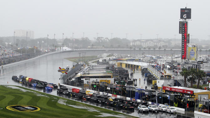 Race cars are parked and covered on pit road during a rain delay before the NASCAR Daytona 500 auto race in Daytona Beach, Fla., Sunday, Feb. 26, 2012. (AP Photo/David Graham)
