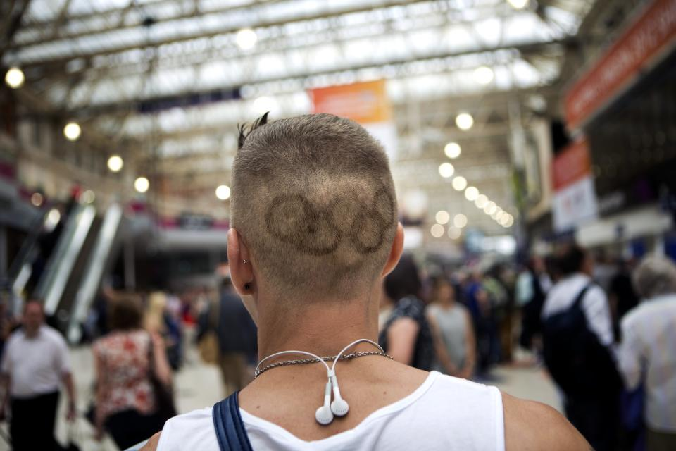 In this Friday, July 27, 2012 photo, a man walks through a train station with the Olympic rings shaved into his hair in London. (AP Photo/Emilio Morenatti)