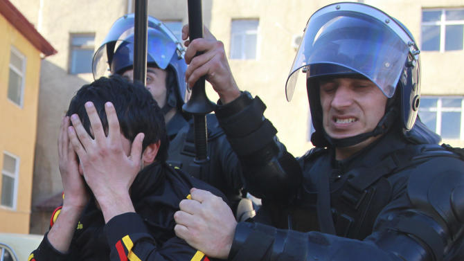 Azerbaijani police officers detain a demonstrator in Ismayilli, some 175 kilometers (110 miles) from the capital, Baku, Azerbaijan, Thursday, Jan. 24, 2013. A minor car accident in a town in central Azerbaijan spiraled into a showdown Thursday between residents and regional authorities, exposing underlying tensions and democratic shortcomings in the oil-rich former Soviet nation. Hundreds of angry demonstrators in Ismayilli surrounded a regional government building Thursday demanding the governor's resignation after a night of rioting in which a hotel and several cars were torched. (AP Photo/Aziz Karimov)