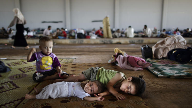 Syrian children, who fled their home with their family due to fighting between the Syrian army and the rebels, lie on the ground, while they and others take refuge at the Bab Al-Salameh border crossing, in hopes of entering one of the refugee camps in Turkey, near the Syrian town of Azaz, Sunday, Aug. 26, 2012. Thousands of Syrians who have been displaced by the country's civil are struggling to find safe shelter while shelling and airstrikes by government forces continue. (AP Photo/Muhammed Muheisen)