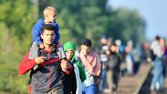 Refugees walk along a railway track at the Hungary-Serbia border, near the town of Horgos, on September 14, 2015