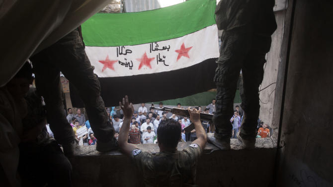"In this Friday, Sept. 21, 2012 photo,  Free Syrian Army rebels hold a revolutionary flag on it during a demonstration in the Bustan al-Qasr neighborhood of Aleppo, Syria. The Britain-based Syrian Observatory for Human Rights said Friday that nearly 30,000 Syrians have been killed during the 18-month uprising against the Assad regime. Arabic on flag is reversed, but reads, ""God welcome, free people."" (AP Photo/ Manu Brabo)"