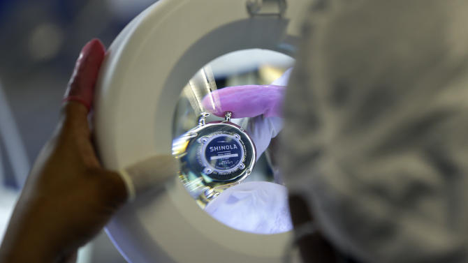 In a photo from April 10, 2013 in Detroit a line worker inspects a wristwatch housing at the Shinola manufacturing facility. Detroit has a long history of making stuff _ cars, steel, even popcorn and is now home to a facility devoted to the production of wristwatches. Shinola officials say their watch production target for this year is 45,000, to be sold online, at flagship stores in Detroit and New York and at fashion and jewelry retailers and department stores around the country. (AP Photo/Carlos Osorio)