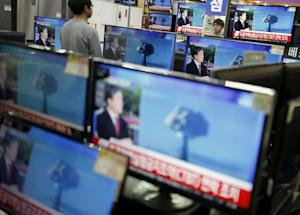 A sales assistant watches TV sets broadcasting a news…