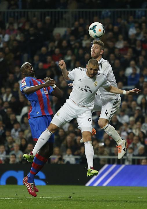 Real's Karin Benzema, center, tries to score between Real's Sergio Ramos, right, and Levante's Mohamed Sissoko during a Spanish La Liga soccer match between Real Madrid and Levante at the