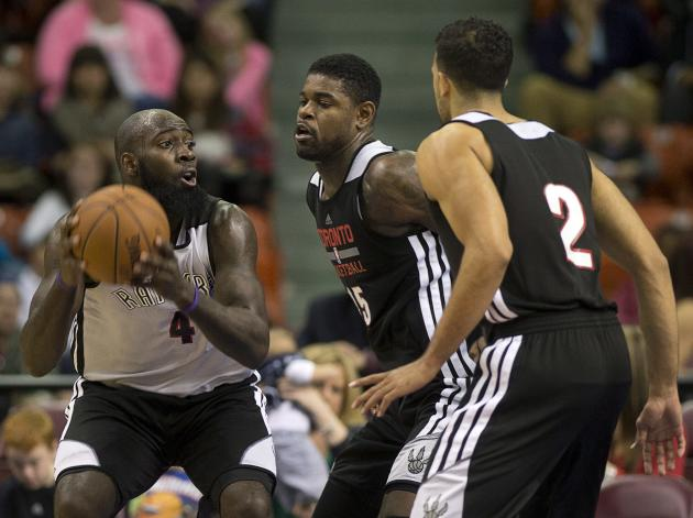 Quincy Acy, left, is defended by Amir Johnson and Landry Fields, right, during the Toronto Raptors' intrasquad NBA basketball game in Halifax, Nova Scotia, on Saturday, Oct. 5, 2013
