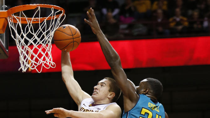 Minnesota's Joey King (24) leaps up to the basket as UNC Wilmington's Addison Spruill (24) defends during the second half of an NCAA college basketball game Saturday, Dec. 27, 2014, in Minneapolis. Minnesota won 108-82. (AP Photo/Stacy Bengs)