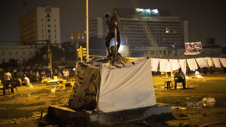 Egyptian men build up a tent in Tahrir Square in Cairo, Thursday, June 27, 2013. Cairo is bracing for mass protests against the government planned for Sunday. (AP Photo/Manu Brabo)
