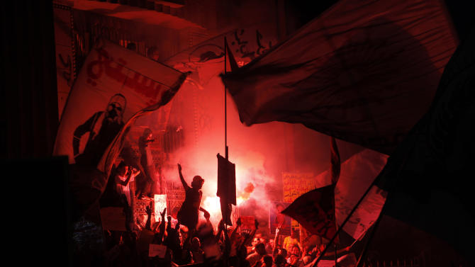AP10ThingsToSee - Members of Egypt's April 6 Youth Movement shout anti-Muslim Brotherhood slogans and light flares during a rally in front of the prosecutor general's office in Cairo, Egypt on Saturday, April 6, 2013. Thousands of activists took to the streets Saturday to mark the fifth anniversary of the founding of a leading opposition group, the April 6 Youth Movement, and to push a long list of demands on Morsi, including the formation of a more inclusive government amid a worsening economy. (AP Photo/Amr Nabil, File)