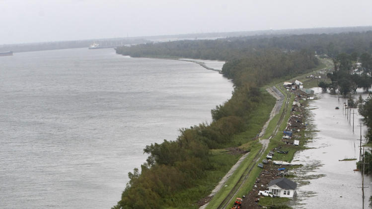 Dislodged homes and debris appear on the levee and submerged roadway in the community of Braithwaite, along side the Mississippi River, seen at left, after Hurricane Isaac came through the region Thursday, Aug. 30, 2012. (AP Photo/Gerald Herbert)