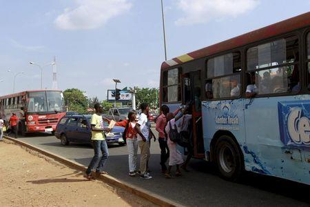 Passengers board a bus at a bus stop, as fuel scarcities persist in Abuja, Nigeria