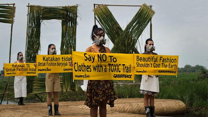 Indonesian models with gas masks wearing dresses by Lenny Agustin, Felicia Budi and Hana Farhana display banners during a fashion show in a polluted river basin in western Java island, March 22, 2015