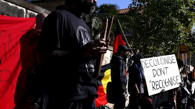 Aboriginal protesters hold banners and chant slogans during a protest outside a government office building in Sydney, Australia