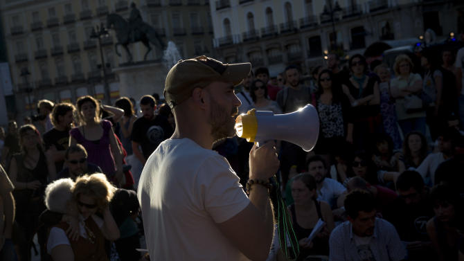 A demonstrator talks   at a protest against the financial crisis and the latest government Economic measures in Sol square,in Madrid Sunday June 10, 2012. Spain's grinding financial misery will get worse this year despite the country's request for a European financial lifeline of up to a euro100 billion euros ($125 billion) to save its banks, Prime Minister Mariano Rajoy said Sunday, a big blow to a nation that took pride as the continent's economic superstar just a few years ago only to see it become the hot spot in the eurozone debt crisis. A day after conceding Spain needed outside help after months of denying it would seek assistance, Rajoy said more Spaniards will lose their jobs in a country where one out of every four are unemployed as the country becomes the fourth and largest of the 17 countries that use Europe's common currency to request a bailout. (AP Photo/Daniel Ochoa de Olza)