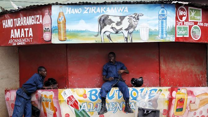 Riot policemen take a break on closed kiosk during clashes with protesters in Burundi's capital Bujumbura