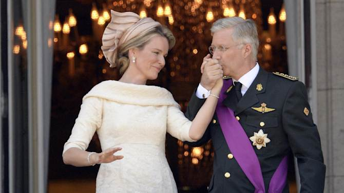 Belgium's King Philippe, right, kisses the hand of Queen Mathilde as they stand on the balcony of the royal palace in Brussels on Sunday, July 21, 2013. Philippe has taken the oath before parliament to become Belgium's seventh king after his father Albert II abdicated as the head of this fractured nation. Earlier Sunday, the 79-year-old Albert signed away his rights as the kingdom's largely ceremonial ruler at the royal palace in the presence of Prime Minister Elio Di Rupo, who holds the political power in this 183-year-old parliamentary democracy. (AP Photo/Geert Vanden Wijngaert)