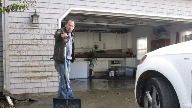 Bill Goldberg shovels mud from the driveway of his home in Point Pleasant Beach, N.J. on Thursday, Nov. 1, 2012. Flooding from Hurricane Sandy inundated his home, and Gioldberg fears he'll have to strip the house down to its wood foundation and rebuild from scratch. (AP Photo/Wayne Parry)