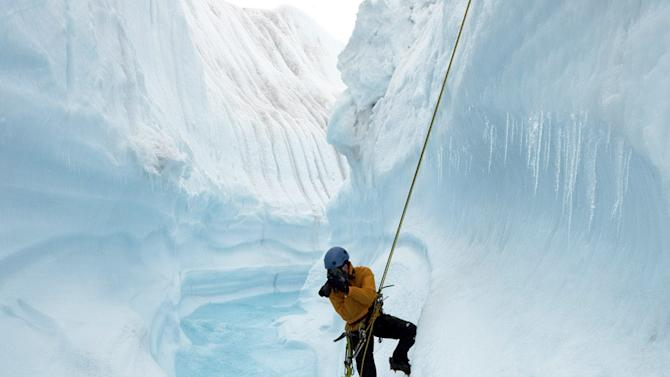 "This 2009 photo released by Extreme Ice Survey shows photographer James Balog rappelling into Survey Canyon in Greenland during the filming of ""Chasing Ice."" The film, about climate change, follows Balog across the Arctic as he deploys revolutionary time-lapse cameras designed to capture a multi-year record of the world's changing glaciers. (AP Photo/Extreme Ice Survey, Jeff Orlowski)"
