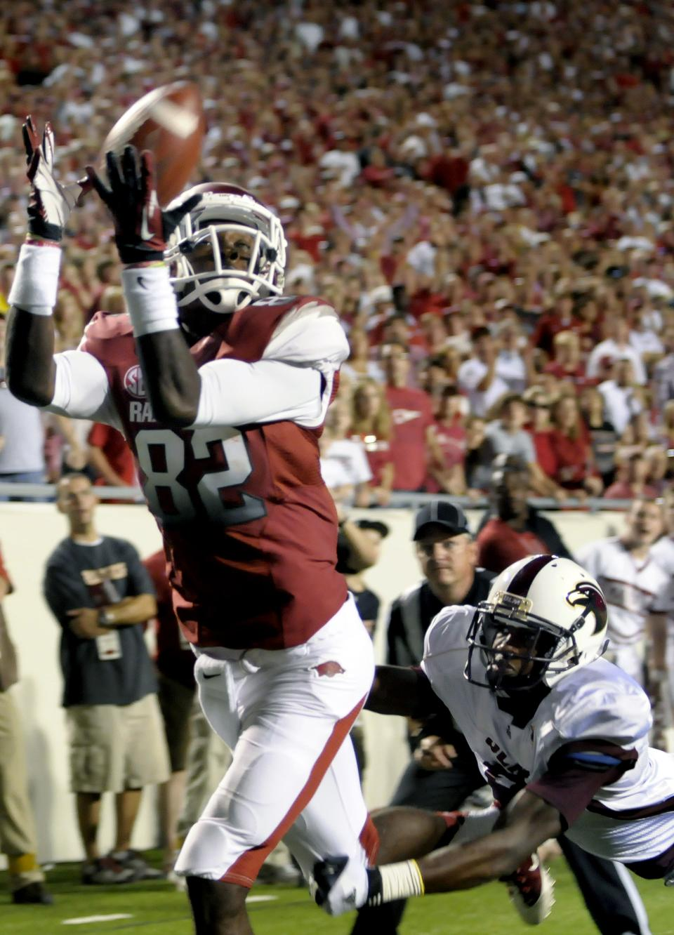 Arkansas wide receiver Mekale McKay (82) catches a 13-yard touchdown pass as he eludes Louisiana Monroe cornerback Otis Peterson, right, during the third quarter of an NCAA college football game in Little Rock, Ark., Saturday, Sept. 8, 2012. (AP Photo/David Quinn)
