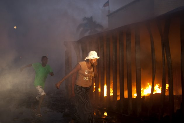 A woman covers her mouth and nose as she walks past an active fire at Port Market in Port-au-Prince, Haiti, Saturday Dec. 29, 2012. Police spokesman Frantz Lerebours said Saturday that dozens of stalls at the popular marketplace were burned to the ground and that few items were recovered. Authorities are investigating what caused the fire late Friday. (AP Photo/Dieu Nalio Chery)