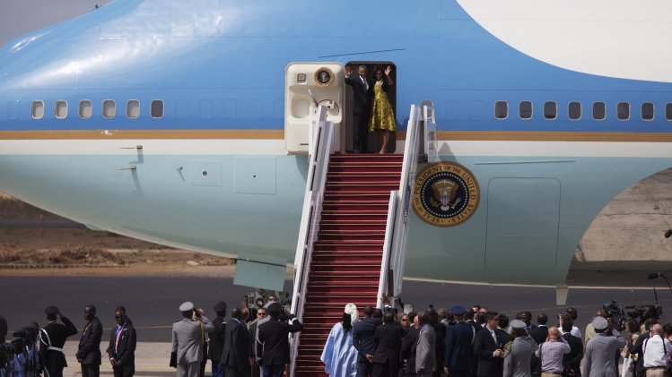 U.S. President Obama and first lady Obama wave before entering Air Force One at the airport in Dakar
