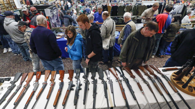 In this Jan. 26, 2013, photo, guns are displayed on a table on display during the annual New York State Arms Collectors Association Albany Gun Show at the Empire State Plaza Convention Center,  in Albany, N.Y. Car dealerships, political parties, hockey teams and, police chiefs see gun giveaways as a way to make money or draw in customers, even after the mass school shooting in Connecticut in December fueled anew the debate over gun buying restrictions. (AP Photo/Philip Kamrass)