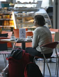 A woman waits with her luggage at Keflavik airport, Keflavik, Iceland Sunday May 22, 2011 as Iceland closed its main international airport and canceled domestic flights as a powerful volcanic eruption sent a plume of ash, smoke and steam 12 miles (20 kilometers) into the air. The eruption was far larger than one a year ago that caused international travel chaos _ but scientists said it was unlikely to have the same widespread effect.