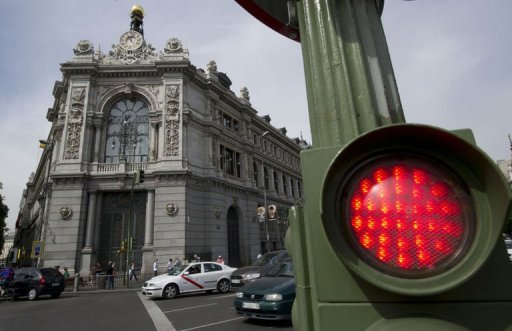 <p>A traffic light is pictured outside the Banco de Espana (Bank of Spain) in Madrid. A job-destroying recession kept a tight grip on Spain in the third quarter of 2012 when output shrank by an estimated 0.4 percent, the Bank of Spain has said.</p>