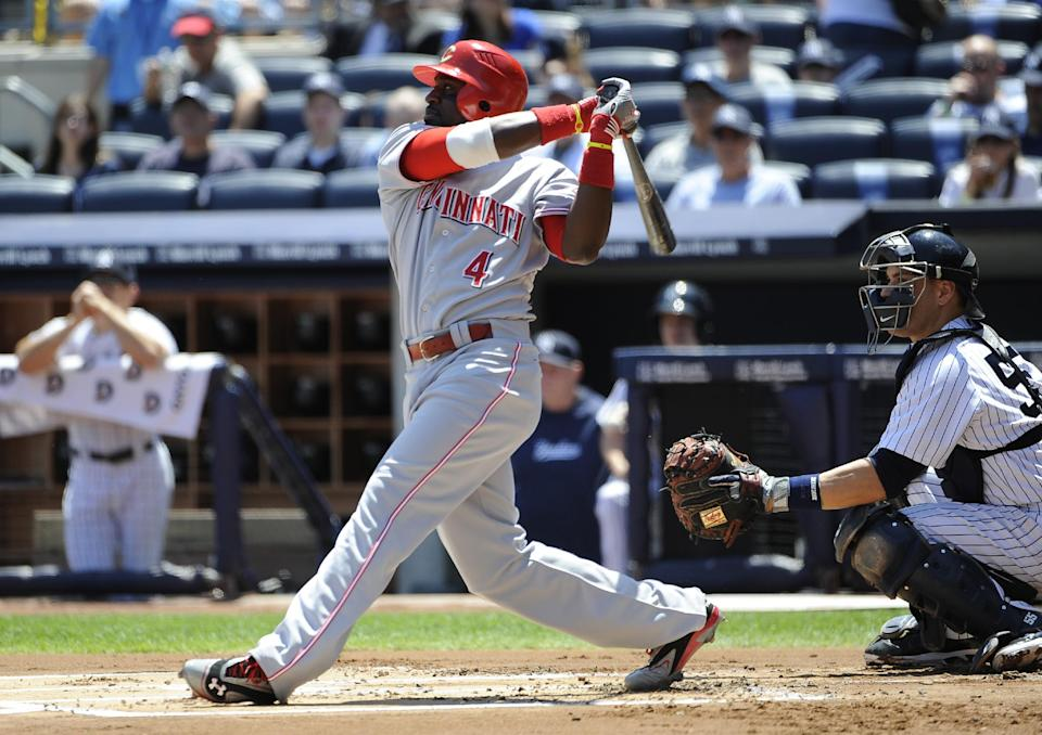Cincinnati Reds' Brandon Phillips (4) hits an RBI single off of New York Yankees pitcher Ivan Nova as catcher Russell Martin looks on during the first inning of an interleague baseball game on Saturday, May 19, 2012, at Yankee Stadium in New York. (AP Photo/Kathy Kmonicek)