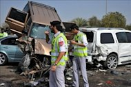Policemen inspect the site of the massive pile-up. The busy highway between the United Arab Emirates' two main cities was closed for hours. Photograph: HO/WAM/AFP